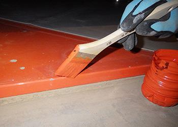 免震鋼材ダンパーをタッチアップしている事例